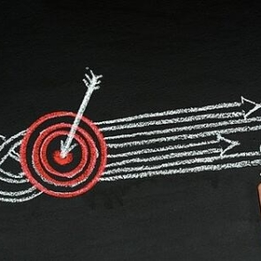 a target and arrows drawn on a blackboard