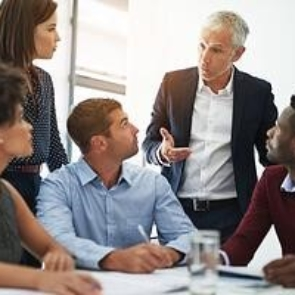 five business people having a conversation in a room