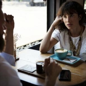 A woman talking to a business man at a table in a cafe