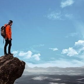 a hiker standing on a cliff edge looking out over a vast view