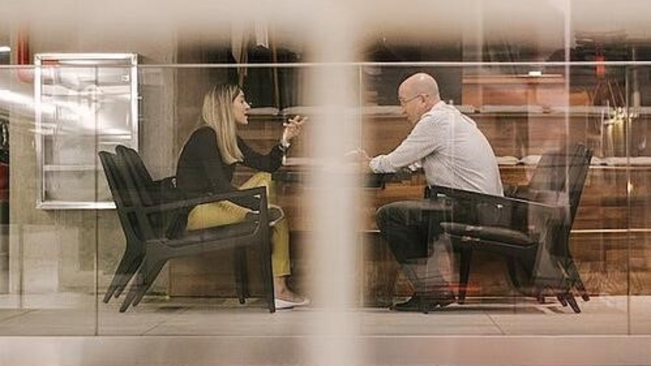 two people in a meeting room talking