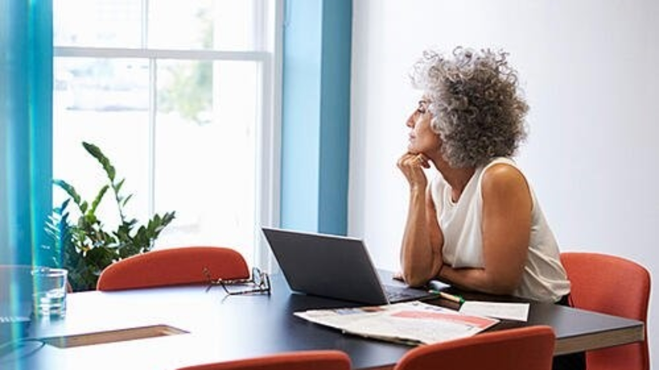 A middle-aged woman on a laptop looking out a window