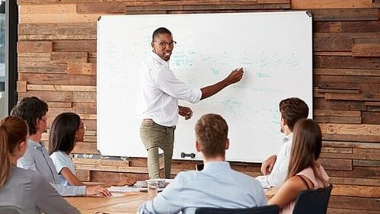 a tutor showing text written on a whiteboard in a classroom