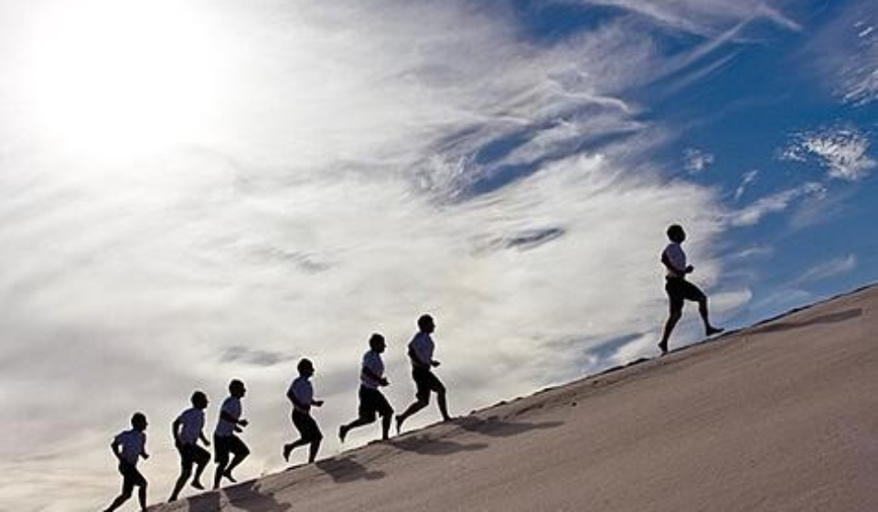 an image of several people running along a beach up hill