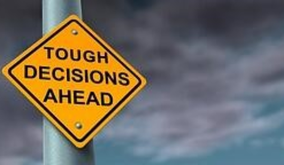 A road sign saying tough decisions ahead